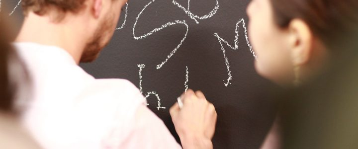 ein mann schreibt mit kreide auf schwarze wand