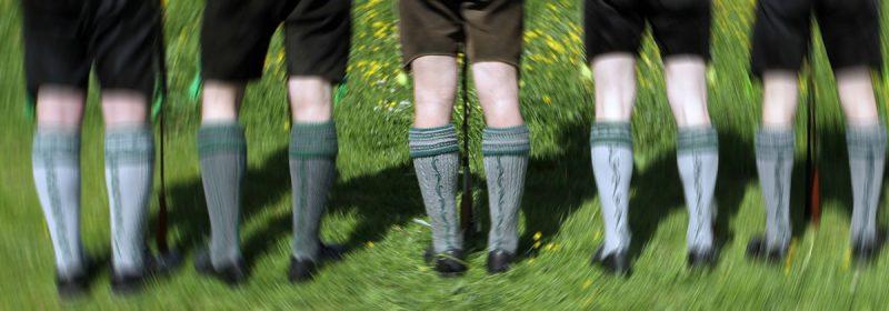 Männerbeine in bestickten stutzen und lederhosen von hinten. das bild wird kreifförmig von der mitte weg immer verschwommener