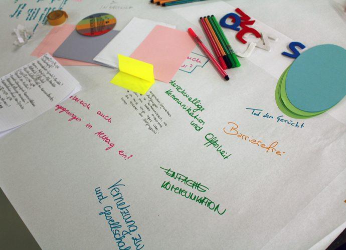 ein tisch ist mit weißem papier bedeckt, stifte und bunte zettel liegen darauf. stichworte sind darauf geschrieben, wei barrierefrei, einfache kommunikation, niederschwellige kommunkiation und offenheit