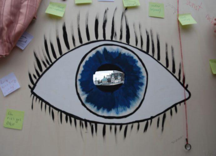 ein auge ist auf einen karton gemalt in der mitte ein loch darin sieht man die festung hohensalzburg