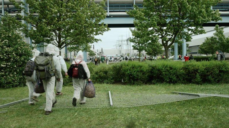 menschen in schutzanzügen gehen über einen umgestürzten zaun auf einer grünfläche
