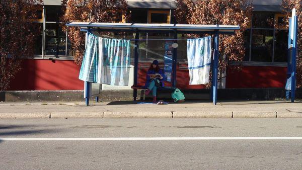 Eine Bushaltestelle, die mit Vorhängen verziert ist. Eine Frau sitzt darin und liest